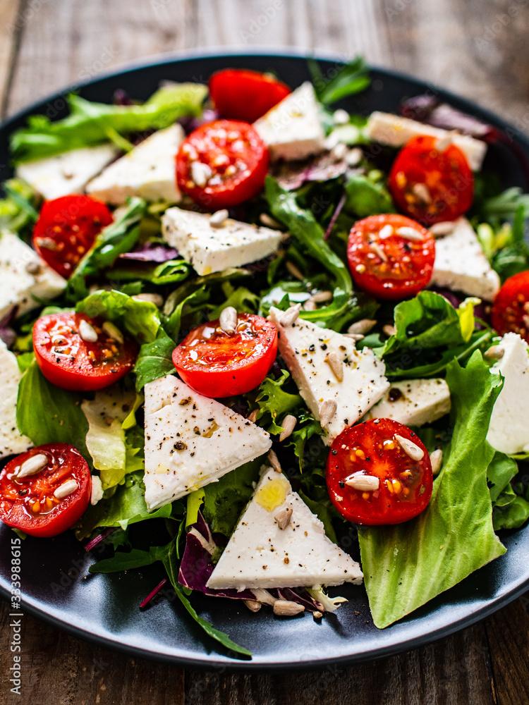 Fototapeta Fresh greek salad - feta cheese, tomato, lettuce, black olives and onion
