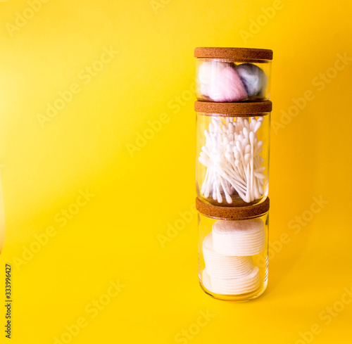 Photo cotton swabs, colored cotton wool ball, cotton discs inside glass small container with wooden top