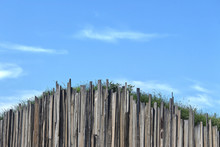 Uneven, Random, Curved Timber Wall Holding Up A Mound Of Ground With Grass. There Is A Blue Sky And Clouds In The Background