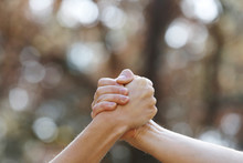 Two People Shaking Hands Isolated On A Natural Background In The Park. Isolate Two Hands Holding On Another, Signal Of Collaboration. Copy Space. Selective Focus