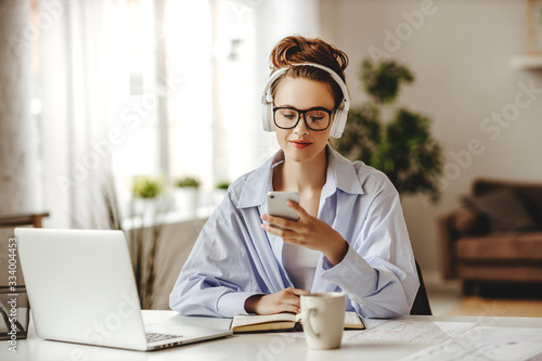 Obraz Satisfied adult woman with coffee using smartphone while working at laptop in light living room. - fototapety do salonu