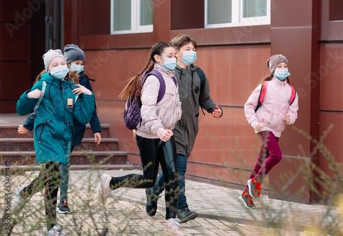 Obraz Children students in medical masks leave the school. - fototapety do salonu