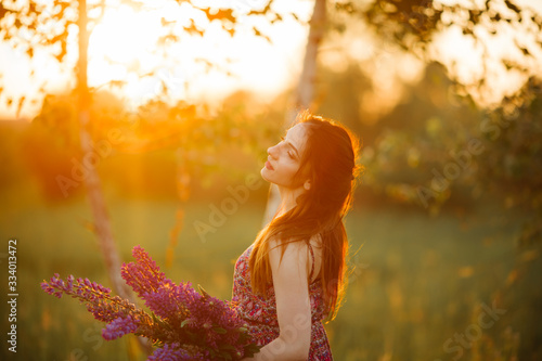 Fototapeta Young girl stand in field overlooking lavender field. Smiling carefree caucasian girl in dress enjoying the sunset obraz na płótnie