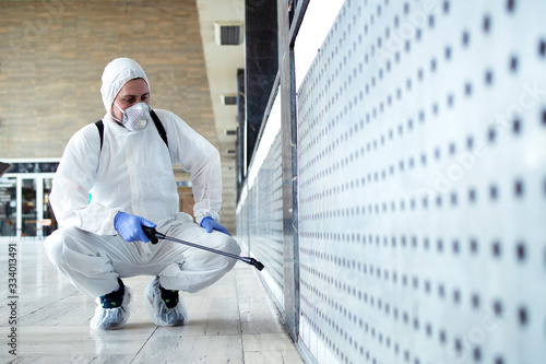 Obraz na płótnie Shot of male person in white chemical protection suit doing disinfection of public areas to stop spreading highly contagious corona virus