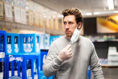 Coronavirus, Mann schützt sich im Laden mit Atemmaske und Handschuhen vor einer Fototapeta