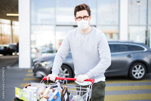 Mann mit vollem Einkaufswagen vor einem Supermarkt, Atemmaske und Handschuhe als Schutzmaßnahme