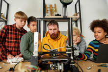 Experience Digital Innovation. Group Of Smart Kids Listening To Their Male Teacher While Looking At 3d Printer And Plastic Detail Prototype At Robotics School Lesson