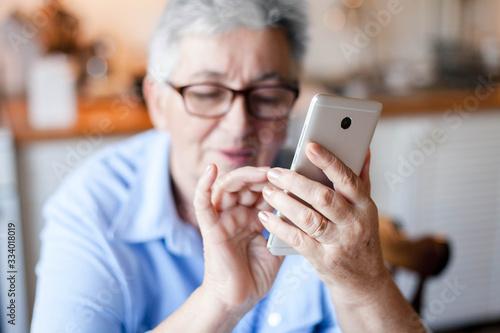 Leinwand Poster Senior woman using mobile phone at home
