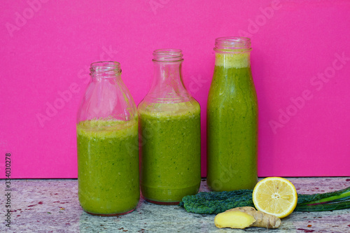 Glass bottles filled with fresh kale and ginger green smoothie