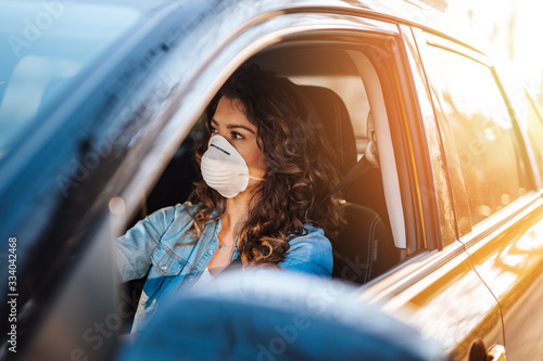 Leinwand Poster Young woman driving car with protective mask on her face