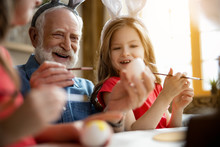 Excited Grandfather And Granddaughter Painting Eggs Stock Photo