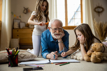 Happy Elderly Man Drawing With Kids Stock Photo