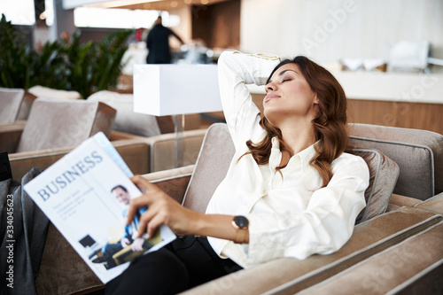 Photo Beautiful young woman resting in armchair at business center