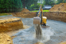 Excavator Digging Bucket Scooping Gravel From A Building Foundation