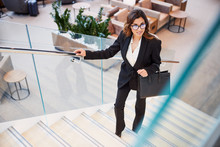 Gorgeous Young Woman Climbing Stairs In Business Center