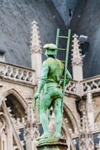Green Sculpture Of Man With Ladder In Front Of Church