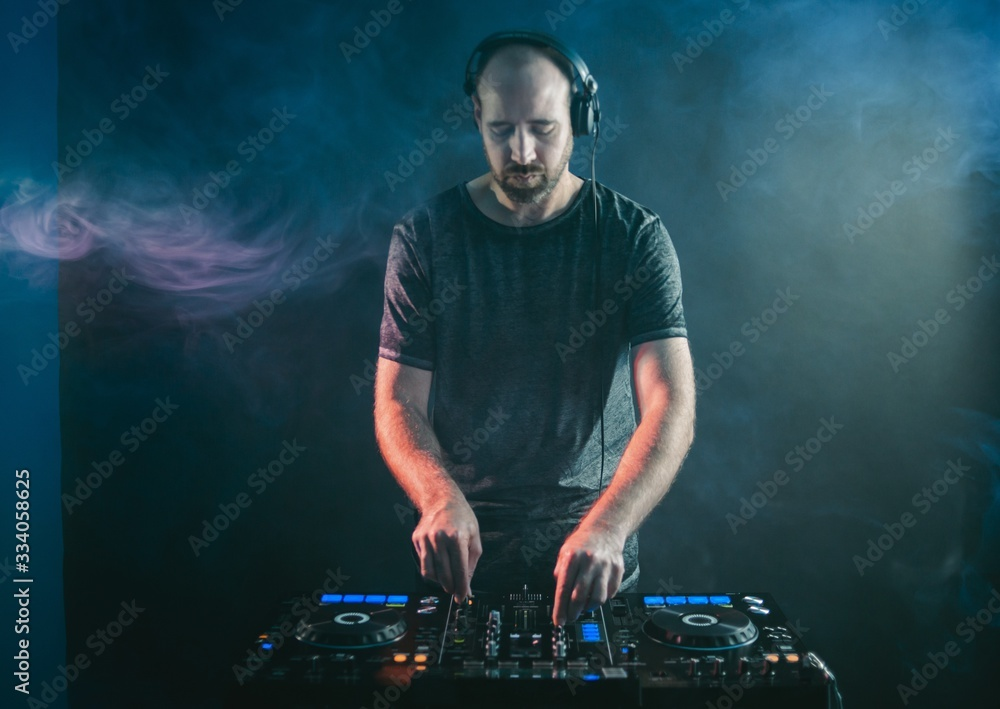 Fototapeta Male DJ working under the blue lights and smoke in a studio against a dark background