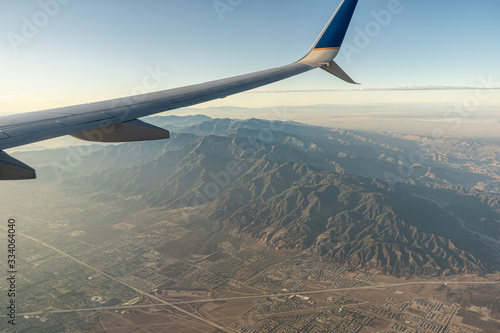 Looking out the window of an airplane soaring high above the buildings and landscape on the ground below Wallpaper Mural