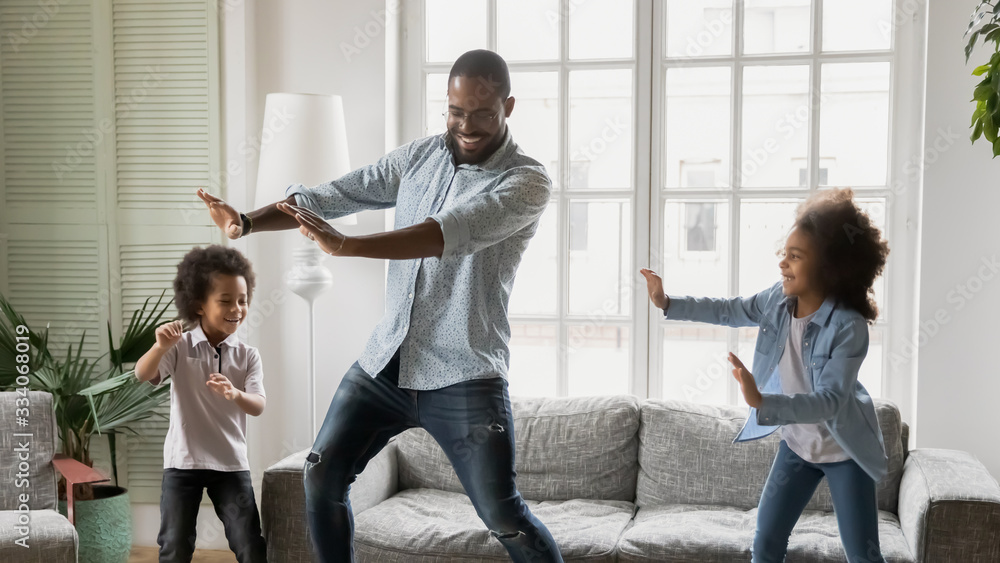 Fototapeta Happy African ethnicity father have fun teaches little preschool kids to dance in modern living room at home. Dad with son and daughter engaged in funny activity enjoy leisure carefree weekend concept
