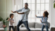 Leinwanddruck Bild - Happy African ethnicity father have fun teaches little preschool kids to dance in modern living room at home. Dad with son and daughter engaged in funny activity enjoy leisure carefree weekend concept