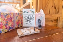 """Closeup Shot Of Event Objects On The Table With A White Panel Entitled """"please Sign Your Guest Book"""""""