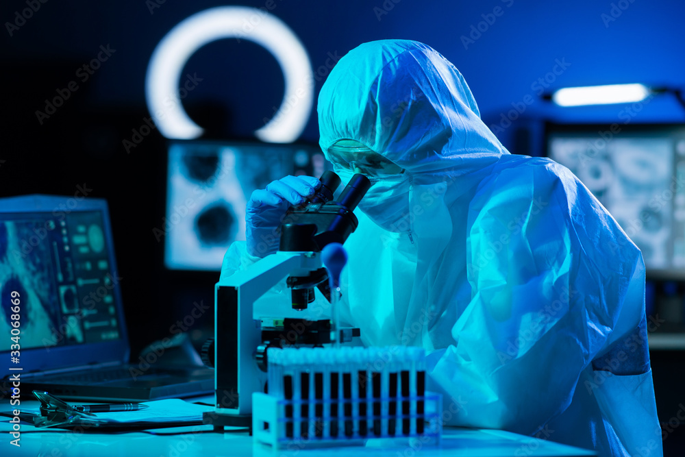 Fototapeta Scientist in protection suits and masks working in research lab using laboratory equipment: microscopes, test tubes. Coronavirus covid-19 hazard, pharmaceutical discovery, bacteriology and virology.