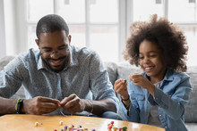African Dad And Little Daughter Sit On Couch Use Colorful Beads Making Bracelet Jewellery Enjoy Pastime Together At Home Activity Promote Development, Fine Hand Motor Skills, Pastime And Hobby Concept