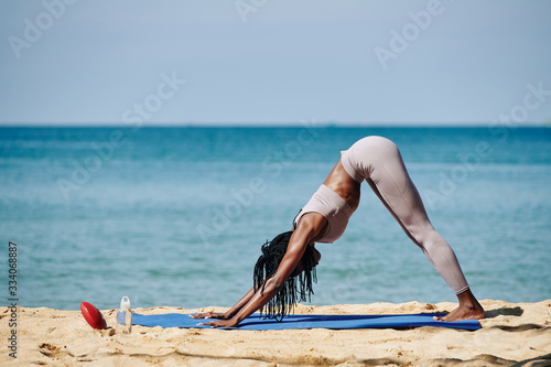 Fit young woman standing in downward facing dog to rest between difficult asanas Fototapeta