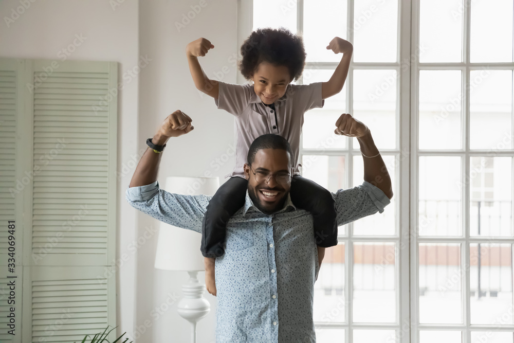 Fototapeta Small son sit on strong dad shoulders showing biceps. African family enjoy activity games at home, healthy fit lifestyle, two superheroes, vitamins for adults and children ad, happy Father Day concept