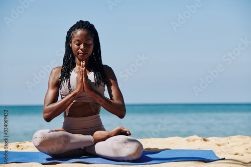 Beautiful slim young woman meditating in lotus position on the beach Fototapete