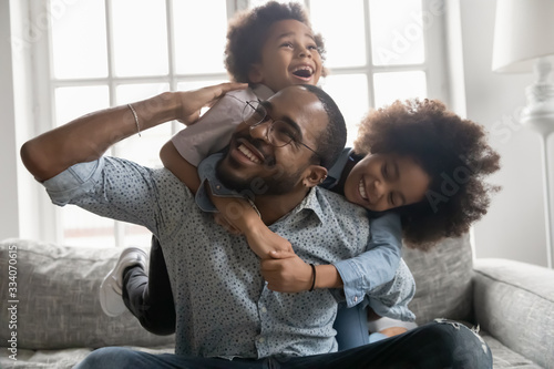 Happy African family at home, cute son and daughter hanging on daddy back, fathe Poster Mural XXL