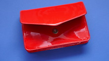 Red Handbag.  Clutch. Women Leather Handbag.Fashion Accessory. Red Patent Leather Clutch On A Bright Blue Background.Fashionable Women's Small Hand Bag In Bright Colors.