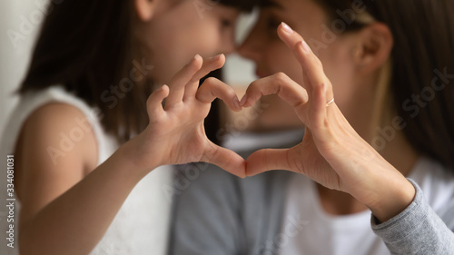 Fotografía Close up of young mother and cute little daughter make heart sign with hands enj