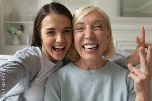 Photo Smiling millennial girl child take selfie with overjoyed funny elderly mother at