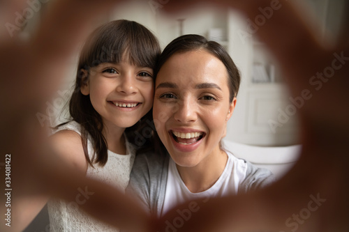 Close up portrait of little girl and young mom or nanny have fun make selfie wit Wallpaper Mural