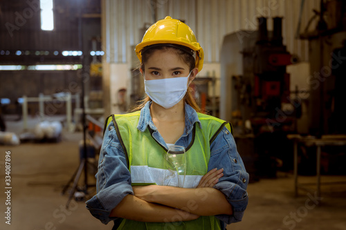 Fototapeta Portrait woman worker under inspection and checking production process on factory station by wearing safety mask to protect for pollution and virus in factory. obraz