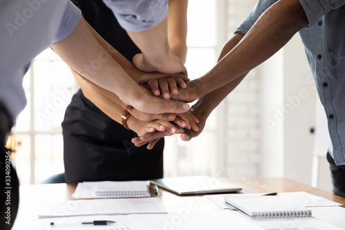 Close up diverse businesspeople stacked their palms together showing support amity and loyalty Canvas Print
