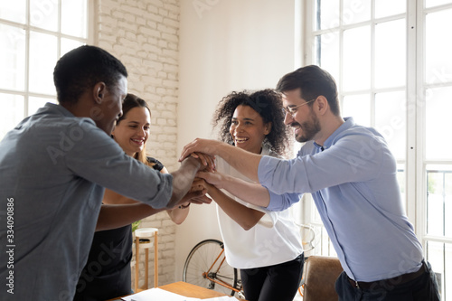 Four millennial different ethnicity teammates stacked palms together feels unity and support Canvas Print