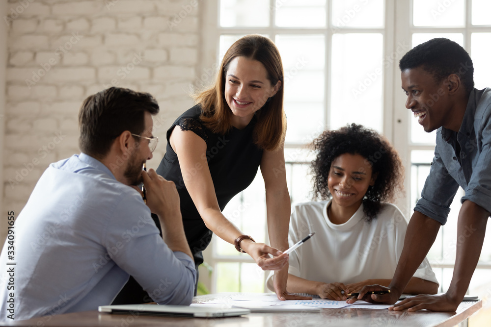 Fototapeta Caucasian woman team leader mentor teach staff multiethnic workers at corporate group briefing explain work results analyzing financial report together, planning project, brainstorming process concept