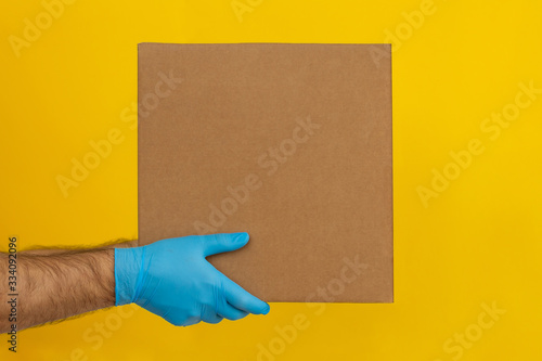 Fényképezés Delivery man holding cardboard boxes on yellow background