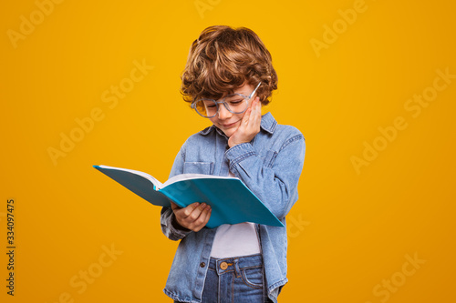 Little boy reading interesting book
