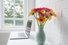 Closeup Of Pink And Orange Gerbera Daisies In Green Vase On White Home Office Desk With Laptop And Window In Background (selective Focus)