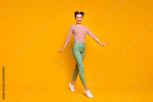 Fototapety, obrazy: Full length profile photo of pretty attractive lady walking down street addicted traveler wear striped red white shirt green trousers sneakers isolated yellow color background