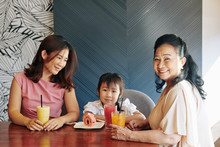 Vietnamese Mother And Grandmother Overindulging Cute Little Girl, Giving Her Tasty Fruit Cocktails And Cakes