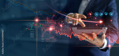 Economic crisis, Businessman using tablet analyzing sales data and economic graph chart that is falling due to the corona virus crisis, Covid-19, stock market crash caused Fototapeta