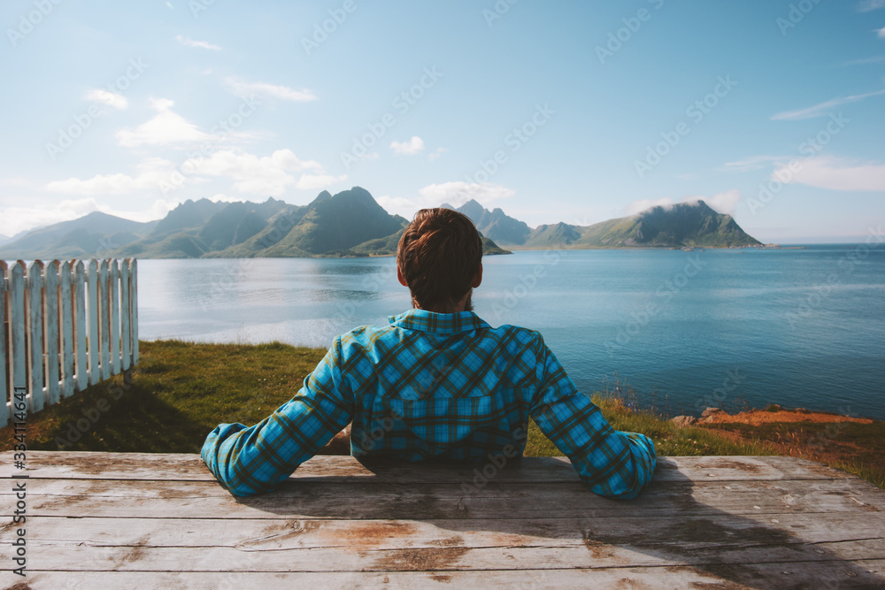 Fototapeta Man relaxing on beach enjoying sea view adventure travel summer vacations outdoor in Norway healthy lifestyle success wellness concept