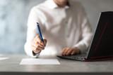 Pracownik w białej koszuli zachęca do podpisania dokumenu, umowy. Długopis w dłoni. Biznesmen przy laptopie w biurze.