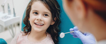 Curly Haired Little Girl Looking And Smiling To The Dentist After A Checking Up