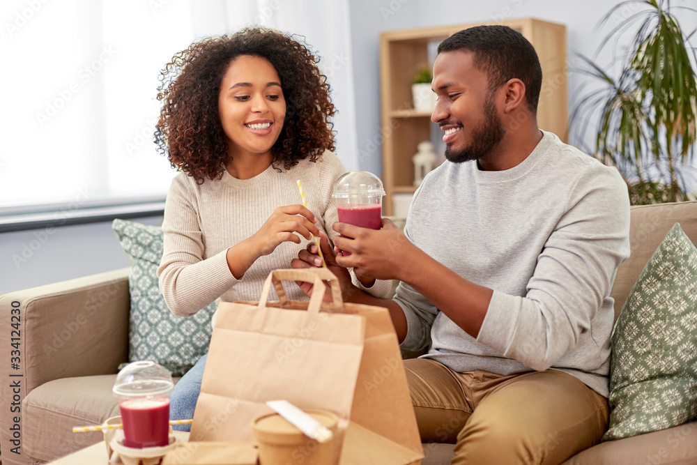 Fototapeta eating and people concept - happy african american couple with takeaway food and drinks at home