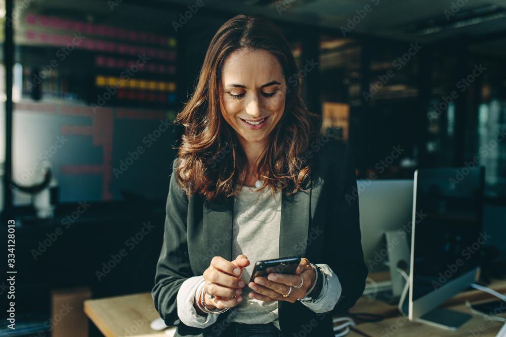 Fototapeta Woman entrepreneur using a phone in office